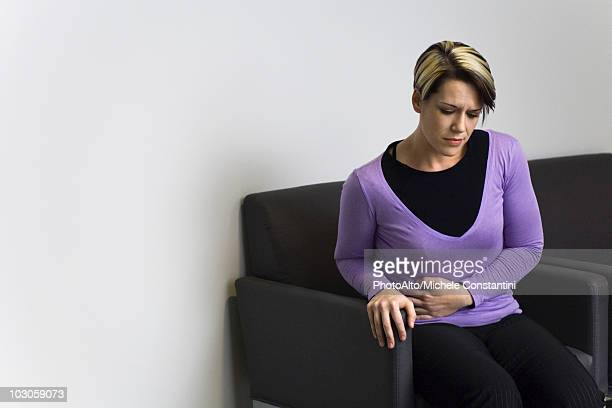 woman sitting in hospital waiting room holding stomach - appendicitis stock photos and pictures