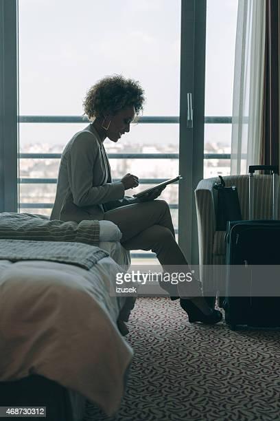 Frau sitzt im Zimmer und Nutzung digitaler tablet