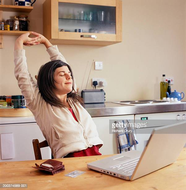 woman sitting in kitchen, stretching arms by laptop - finishing stock pictures, royalty-free photos & images