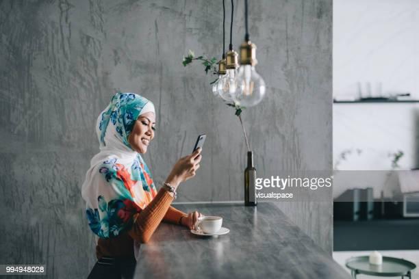 彼女のスマート フォンを使用して、台所に座っている女性。
