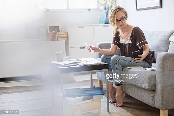 Woman sitting in living room and paying bills using electronic banking