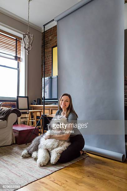 Woman sitting in living room with fluffy dog