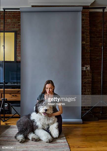 Woman sitting in living room with pet dog