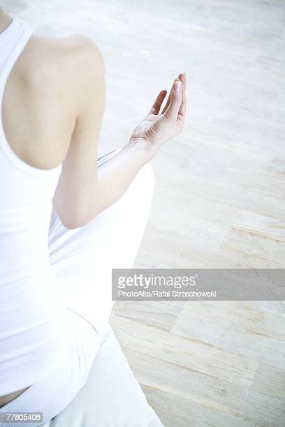 Woman sitting in lotus position, cropped rear view