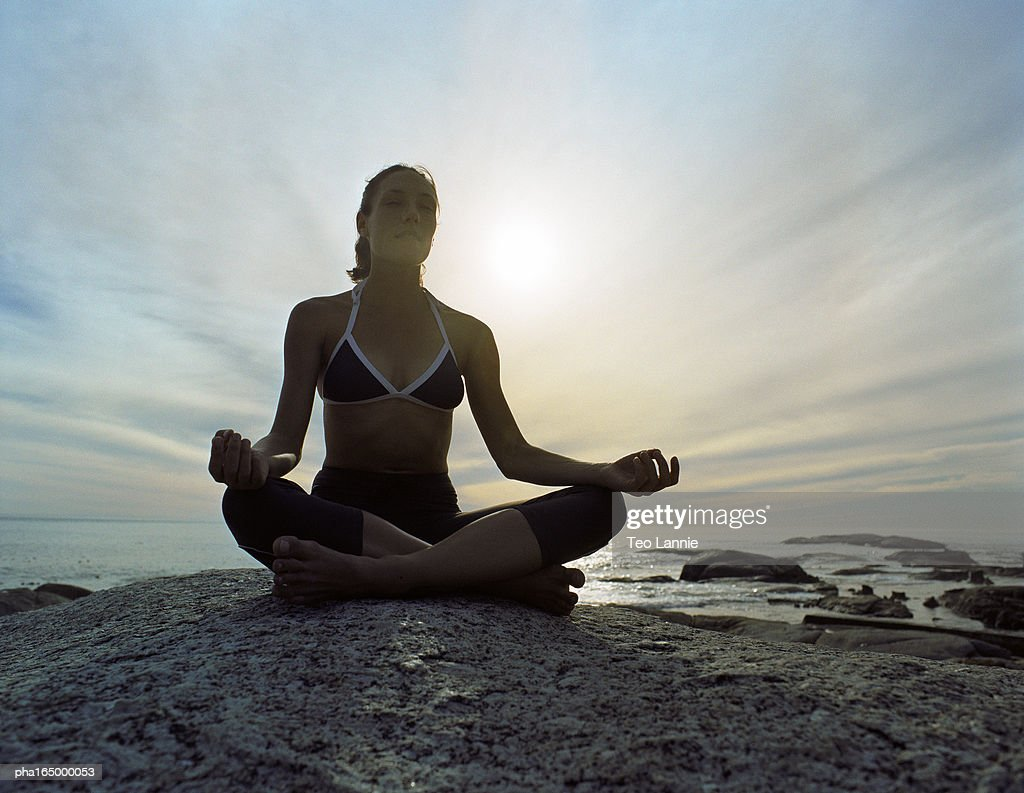 Woman sitting in lotus position, full length, sky and seascape in background : Stockfoto