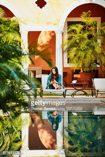 Woman sitting in lounge chair by hotel pool working on smartphone