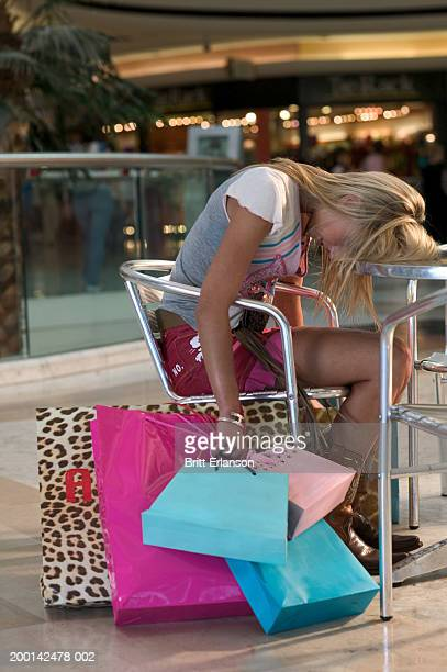 Woman sitting in mall, holding shopping bags, head resting on table