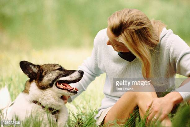 Woman sitting in meadow with dog