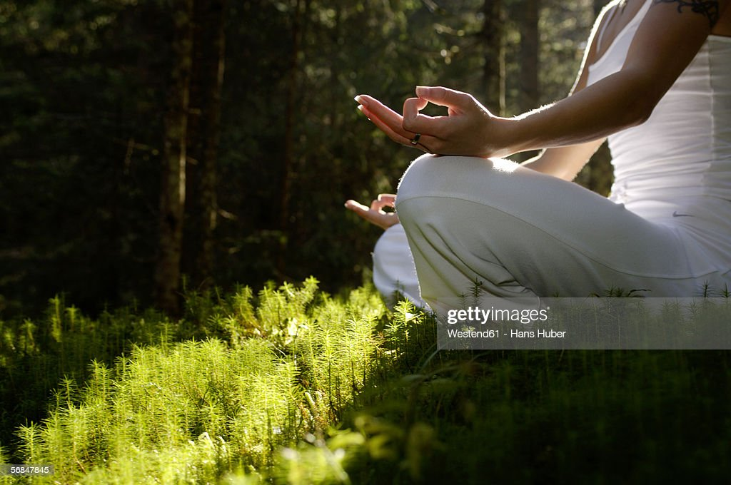 Woman sitting in meditating position outdoors, low angle view : Stock Photo