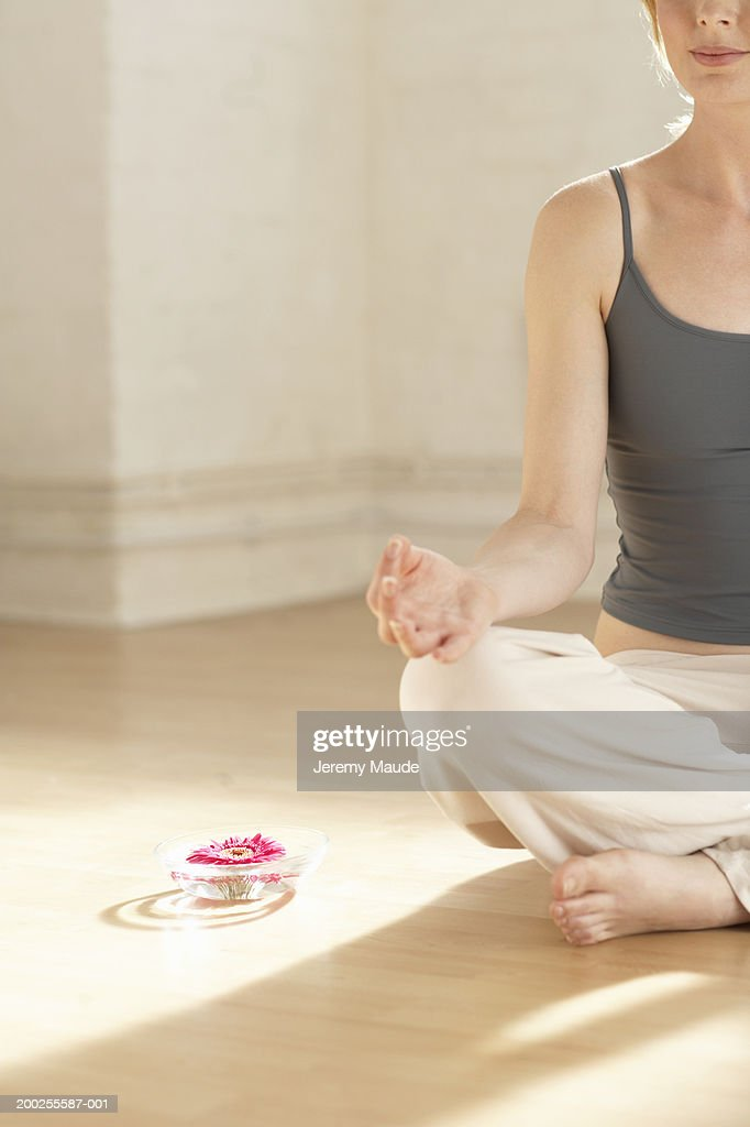 Woman sitting in meditation by flower in bowl : Stock Photo