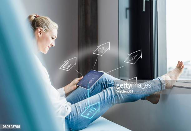woman sitting in office, using digital tablet to remote-control his smart home - house icon stock pictures, royalty-free photos & images