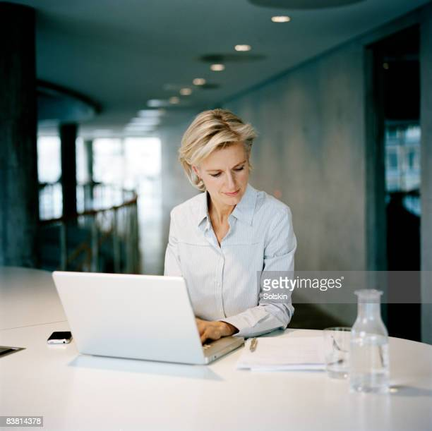 woman sitting in office, using laptop