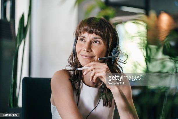 woman sitting in office, wearing headset - employee appreciation stock pictures, royalty-free photos & images