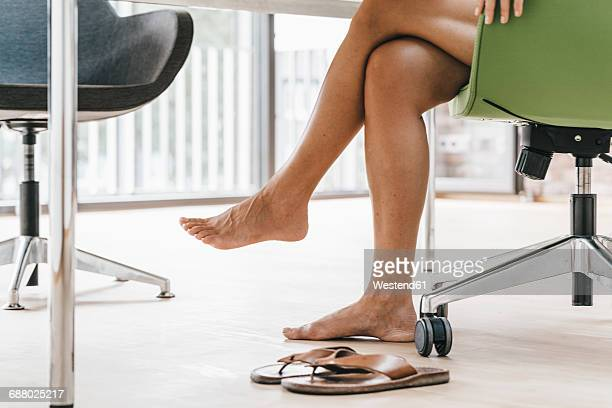 woman sitting in office with bare feet - older woman legs stock photos and pictures