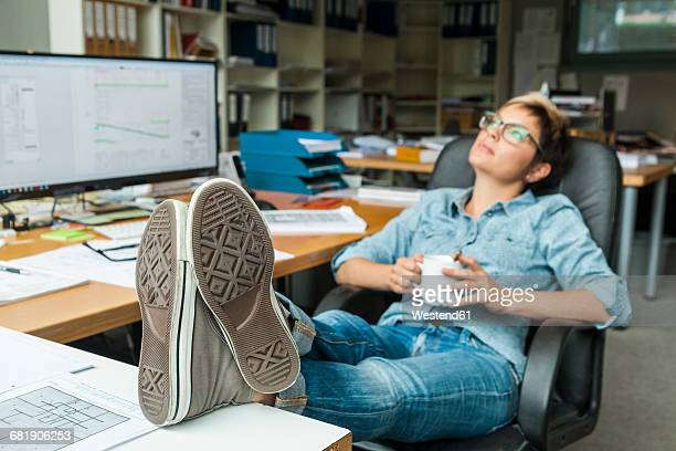 woman sitting in office with feet up, taking a break - woman soles stock photos and pictures