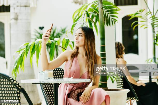 Woman sitting in outdoor cafe taking selfie with smartphone