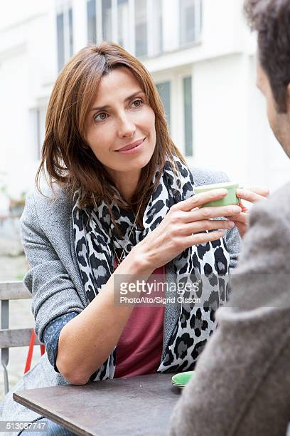 Woman sitting in outdoor cafe with man