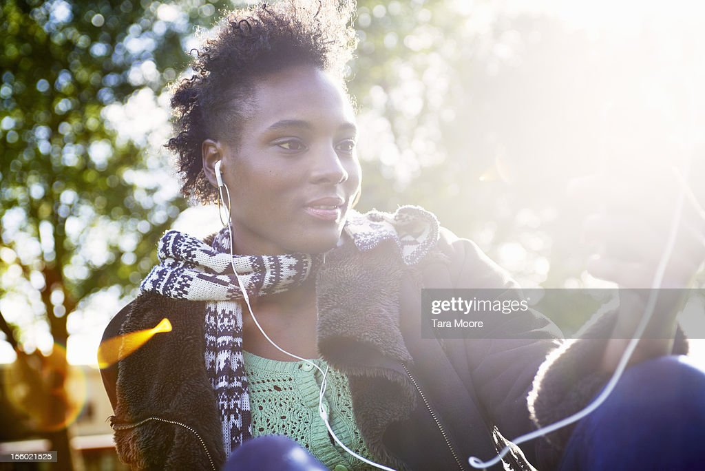 woman sitting in park with ear phones and mobile : Stockfoto