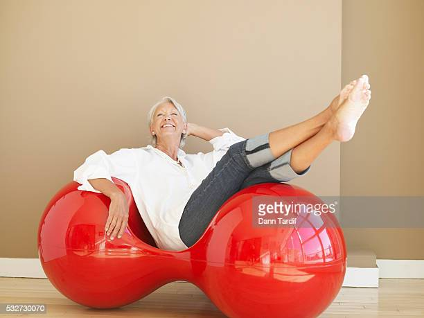 Woman Sitting in Red Designer Chair
