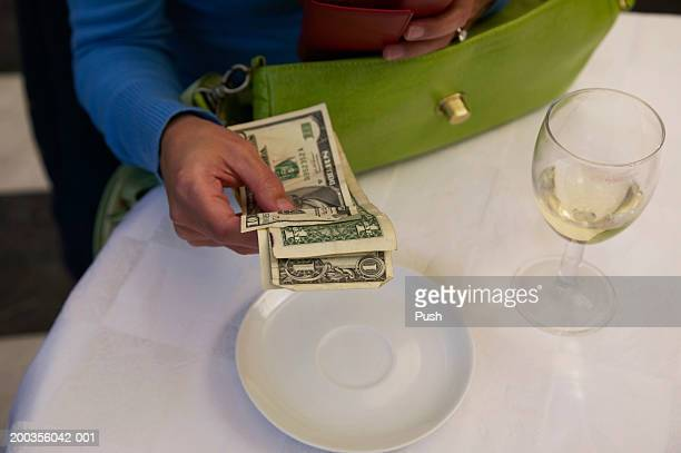 Woman sitting in restaurant, holding dollar banknotes, close-up