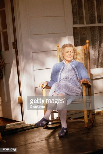 Woman Sitting In Rocking Chair On Porch High Res Stock