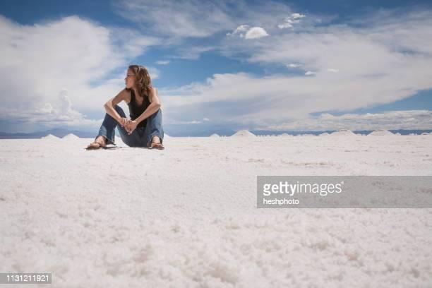 woman sitting in salt field, argentina, salinas grandes, cordoba province, argentina - heshphoto ストックフォトと画像
