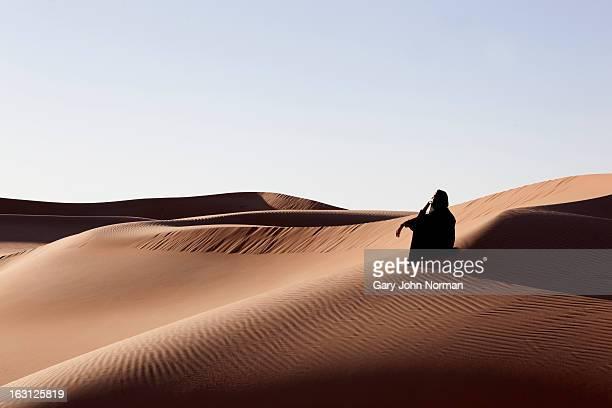 Woman sitting in sand dunes in desert