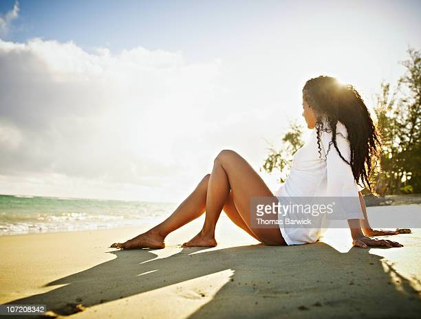 Woman sitting in sand on tropical beach