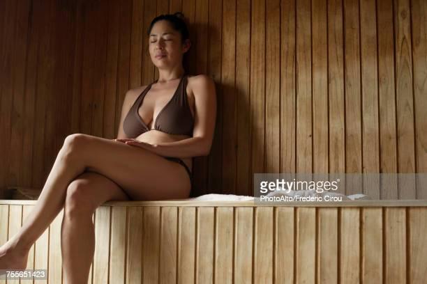 woman sitting in sauna - monokini photos et images de collection