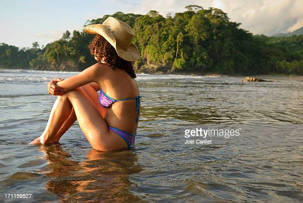 Woman sitting in sea at Playa Ventanas, Uvita, Costa Rica