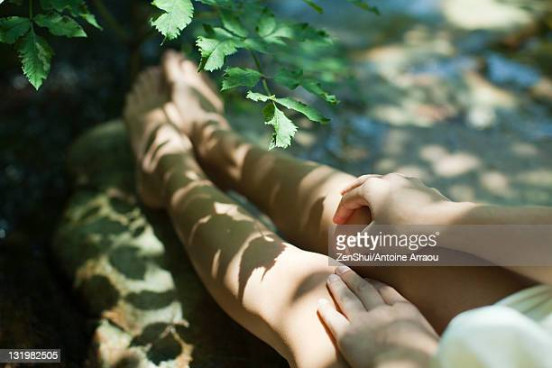 Woman sitting in shadow of tree branches, cropped