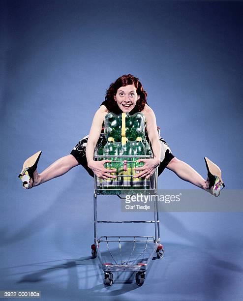 woman sitting in shopping cart - caddie rempli photos et images de collection