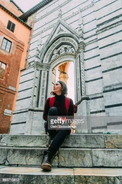Woman sitting in  Siena near Duomo
