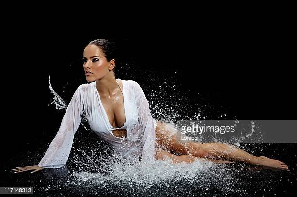 woman sitting in splashing water - wet shirt stock photos and pictures