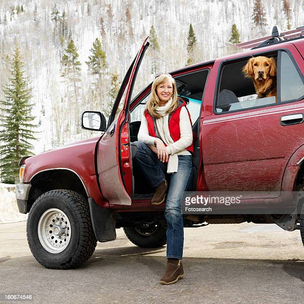 Woman sitting in SUV with dog