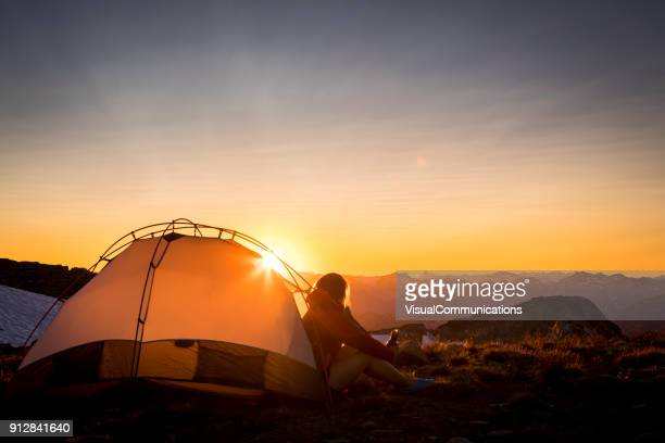 woman sitting in tent looking at sunset. - whistler british columbia stock pictures, royalty-free photos & images