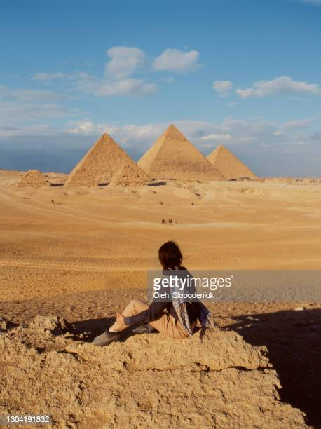 woman sitting in the desert near the giza pyramids - egypt stock pictures, royalty-free photos & images