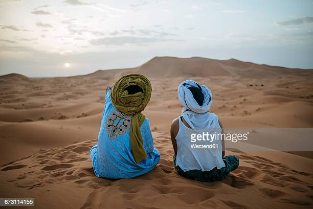 woman sitting in the desert with berber guide, watching sunset - berber photos et images de collection