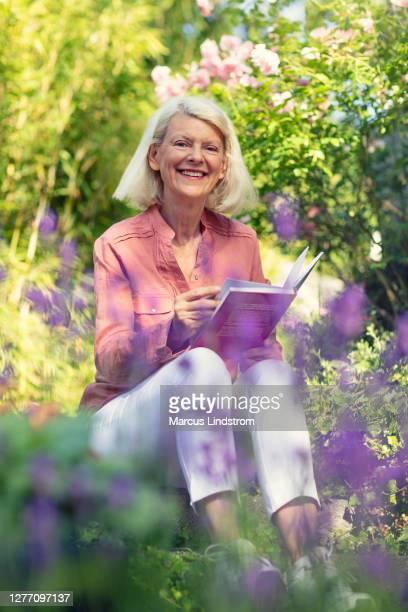 kvinna som sitter i trädgården med en bok - litteratur bildbanksfoton och bilder