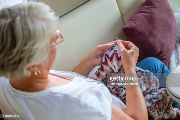 woman sitting in the sofa knitting a scarf - finn bjurvoll stock photos and pictures