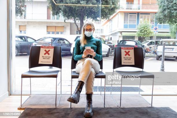 woman sitting in the waiting room - lining up stock pictures, royalty-free photos & images
