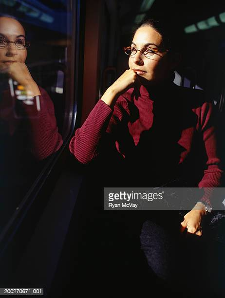 Woman sitting in train looking out window