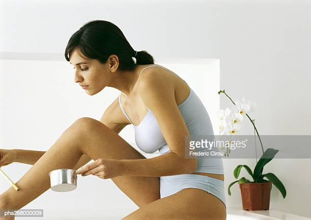 woman sitting in underclothes applying hot wax to leg - epilation maillot photos et images de collection