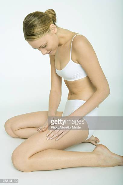Woman sitting in underclothes, touching legs