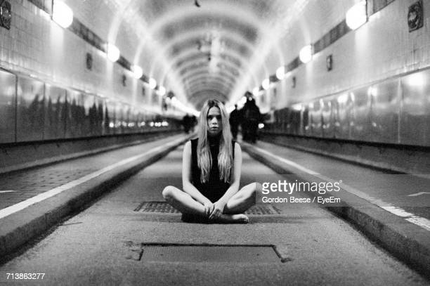 Woman Sitting In Underground Walkway