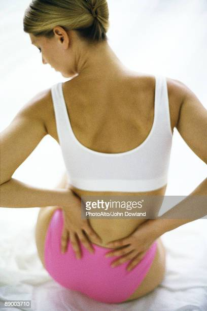 woman sitting in underwear, holding lower back - 下背部 ストックフォトと画像
