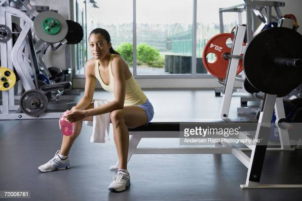 Woman sitting in weight bench at gym
