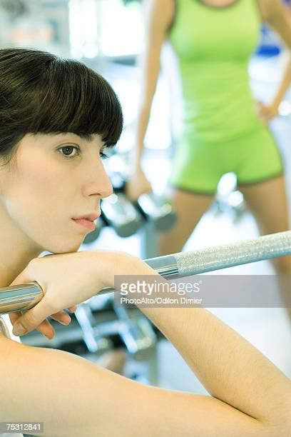Woman sitting in weight room, holding on to metal bar, looking away