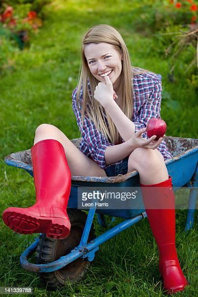 Woman sitting in wheelbarrow in garden