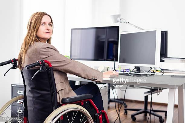 Femme assise dans un fauteuil roulant de travail de bureau moderne
